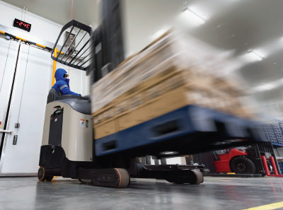Forklift moving frozen food in a cold warehouse