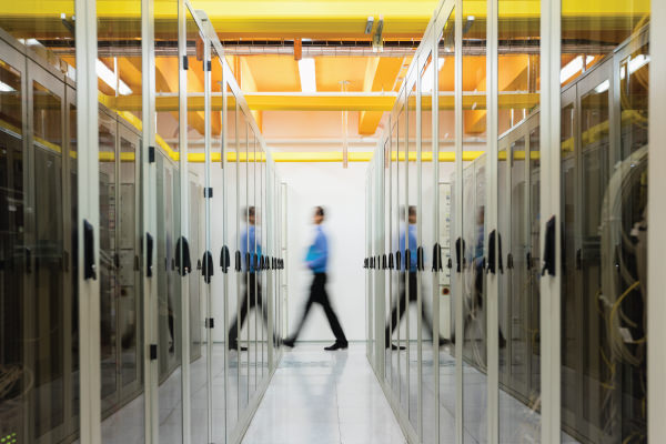 An IT professional is blurred as he walks past two rows of server racks.