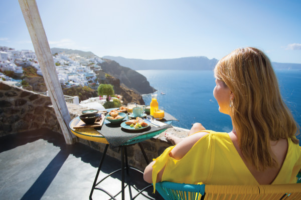 Woman enjoying breakfast on her hotel balcony in Santorini
