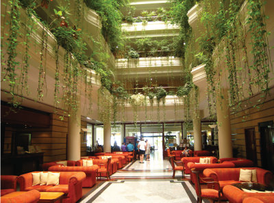 Guests congregate in a tall hotel lobby with plentiful plants