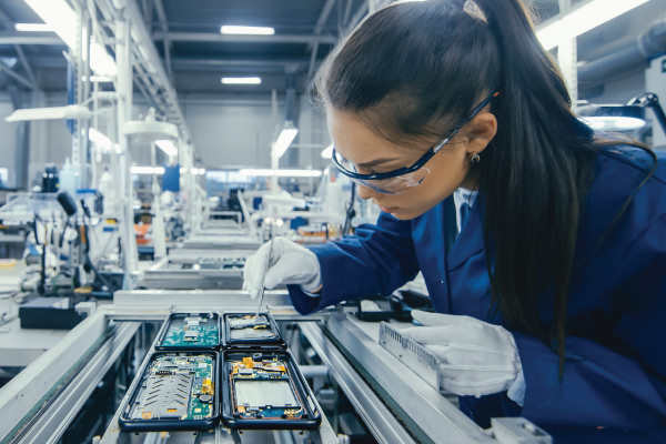 Female technician in an assembly line placing a component on a cell phone circuit board.