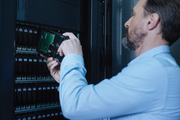 IT technician removing hard drive from server rack